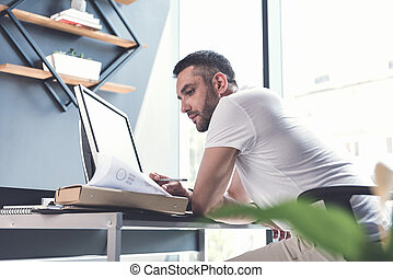 Serious bearded employee is reviewing documents - Adult...