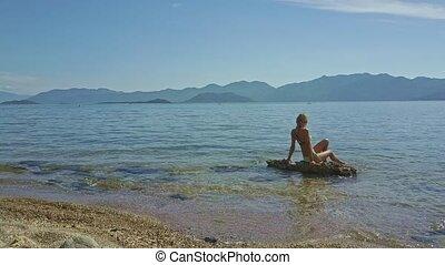 Girl in Bikini Sits on Stone in Sea by Pebble Beach - girl...