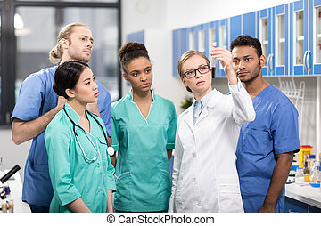 group of medical workers analyzing test tube in laboratory