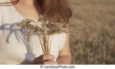Woman Holding Wheat Bouquet - Woman wearing white shirt...