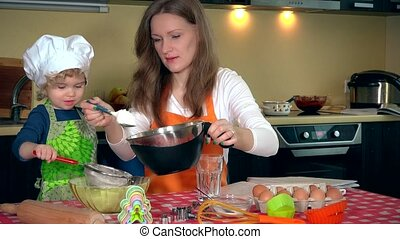 Happy woman with his adorable daughter girl sifting flour for cake baking
