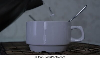 Tea, coffee, water poured into a white cup. Slow motion