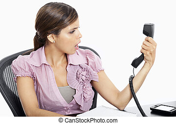 Latina Businesswoman in shock, holding receiver