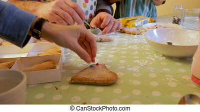 Making Christmas Biscuits - Little boy is adding decorations...