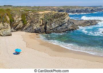 Beach umbrella in Buizinho beach in Porto Covo, Alentejo,...