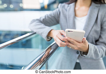 Businesswoman sending text message on mobile phone