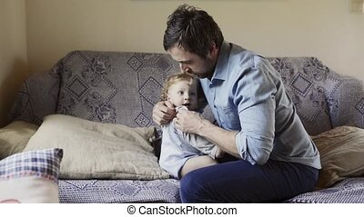 Young father at home with his little son changing his...
