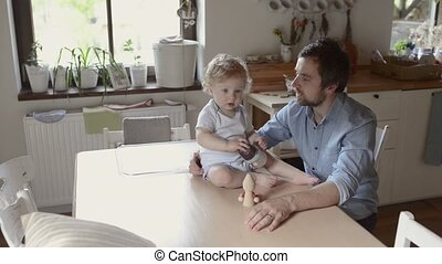 Young father at home with his cute little son. - Young...