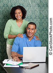 Happy young couple with household bills and laptop at table...