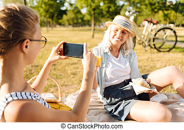 Pleasant teenager girl taking photos of her grandmother on a picnic