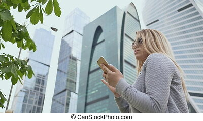 Beautiful girl of the blonde in sunglasses use of mobile phone against the background of the city center.