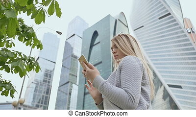Beautiful girl of the blonde use of mobile phone against the...
