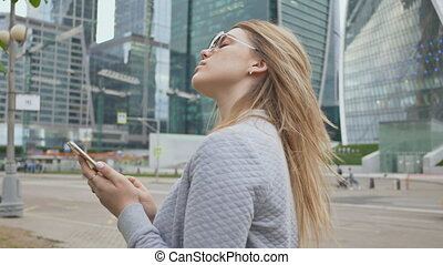 Beautiful girl of the blonde in sunglasses use of mobile...