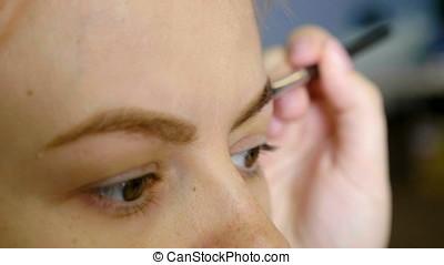 Makeup artist applies paint henna on trimmed eyebrows. Close...