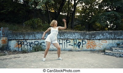 Woman dancing modern choreography in city park outside City...