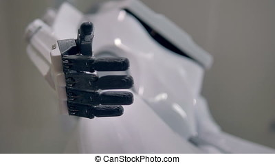 A resting robots palm with black fingers contracting to a...