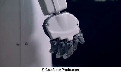 Robots resting arms with black fingers slightly bending. -...