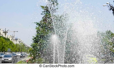 Water drops from fountain in city splashing on water...