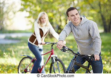 Couple on bicycles - A man on a bicycle in the park in the...