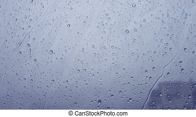 Rain drops running down on a window pane. Blue tint. - Storm...