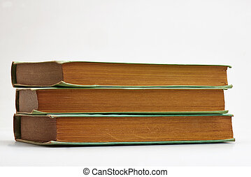 Three old books stacked on white background