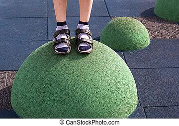 Children's feet at the playground balance equipment -...