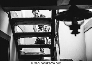 Father at home with his little son walking slowly up the stairs.