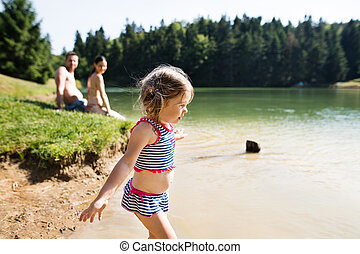 Mother, father and daughter at the lake. Sunny summer. -...
