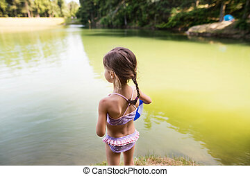 Little girl standing at the lake. Sunny summer. - Cute...
