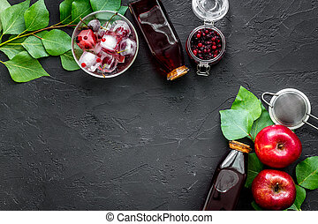 Summer ice fruit drink with apple and cranberry on black table top view copyspace