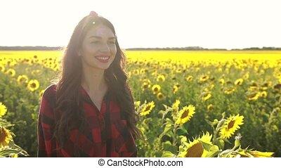 Delighted girl enjoying summer in sunflower field