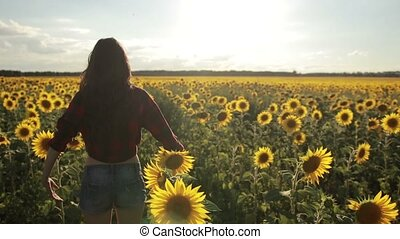 Girl standing with arms raised in sunflower field - Back...