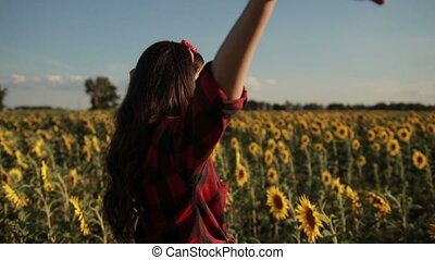 Woman with arms raised relaxing in sunflower field -...