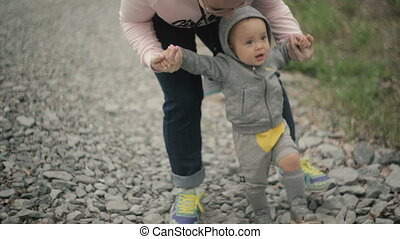 Funny little boy learns to walk. His hands are supported by...