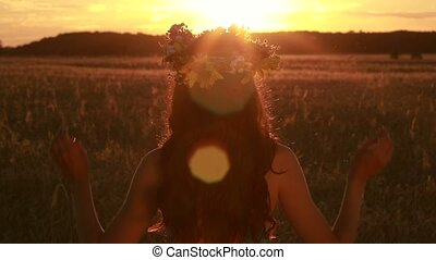 Calm woman holding flower wreath in twilight time