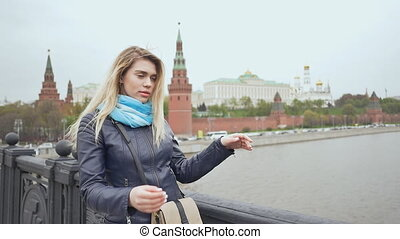 Young beautiful woman posing on the bridge on the background Red Square, Moscow Kremlin, Russia