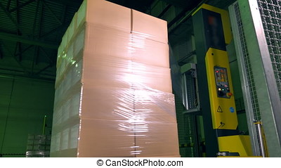 A vertical machine covering rotating boxes with wrap. - An...