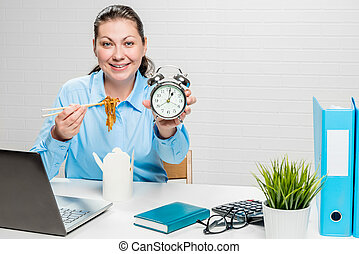 Girl accountant in the office with noodles and an alarm...