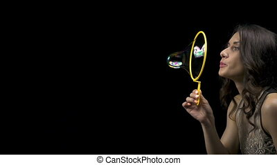 Young brunette girl and soap bubbles on black background