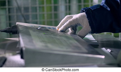A worker in cotton gloves using an industrial keyboard. - A...