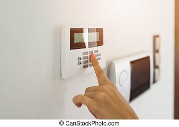 Young woman entering authorization code pin on home alarm...