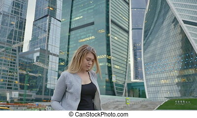 The girl is in a good mood walking through the city in the center of the city against the backdrop of skyscrapers and high-rise buildings. Shooting in slow motion.