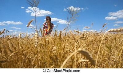 beautiful happy girl is standing in a wheat field on the sky...