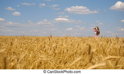 beautiful girl standing in a wheat field, smiling and straightens the hair