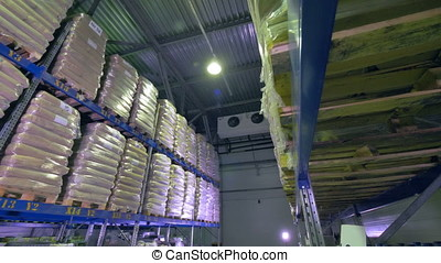 A warehouse corridor sided by shelving units. - A low angle...