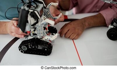 Two top sawyers working on robotic machine together -...