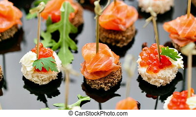 the buffet at the reception. Assortment of canapes. Banquet service. catering food, snacks with salmon and caviar. rye, wheat bread.