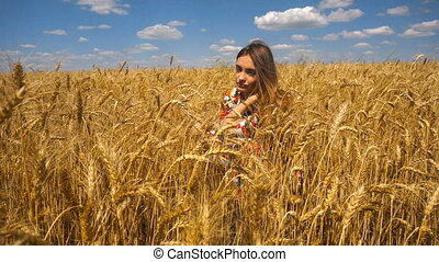 young girl sits in a wheat field and looks into the camera