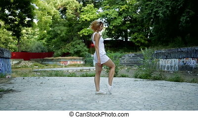 Young Asian woman dancing modern choreography in city park, outside. City ruins and graffiti Hip-hop