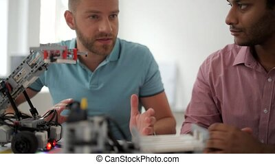 Male colleagues working on engineering project together -...
